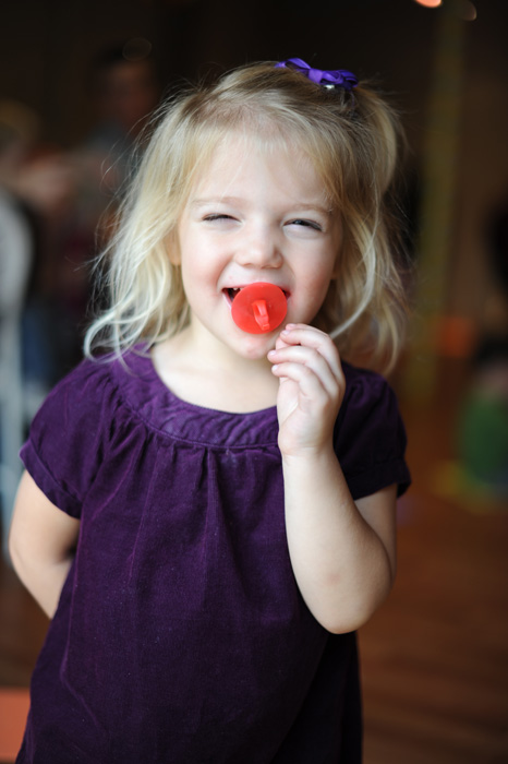 happy girl at birthday party eating ring pop