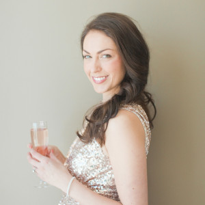 Brunette in golden sequin dress holding a glass of pink champagne