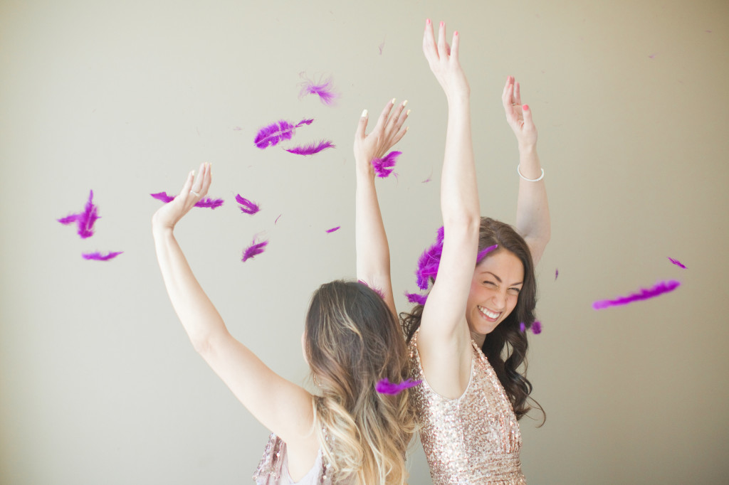Two girls in sequin dresses throwing purple feathers in the air